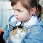 a child holding a cat